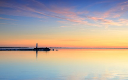 lighthouse in the sea at the colorful sunset