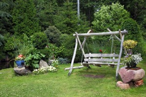 Wood swing in the green garden