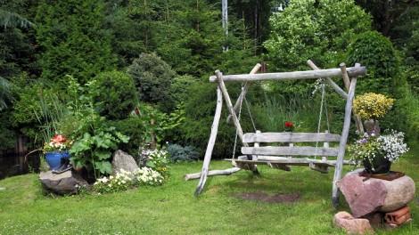 Wood swing in the green garden